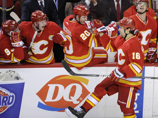 Calgary Flames' Tom Kostopoulos celebrates his goal against the Philadelphia Flyers with Curtis Glencross and teammates