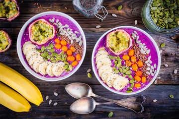 Blueberry smoothies bowl with sea-buckthorn, banana, passion fruit, chia seeds, pumpkin seeds, sunflower and flax seeds