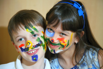 Joyful children with paints on their faces.