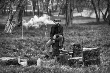 Vape man. Photo of a brutal bearded young man having rest after chop firewood and vaping an electronic cigarette in the village. Black and white photo. Lifestyle.