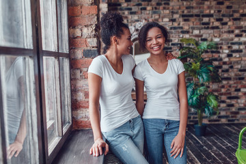 Two attractive african american girls in white T-shirts are standing near the window.