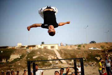 A member of Bar Palestine team demonstrates his street workout skills during a training session on a beach in Gaza City