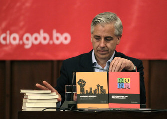 Bolivia's vice president Garcia Linera looks at the books of British author and academic Harvey at a conference in La Paz