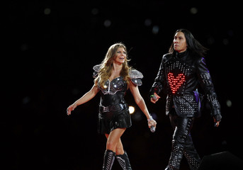 Black Eyed Peas walk off the stage following the group's performance during half-time of the Super Bowl in Arlington