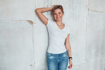 Attractive blonde woman in a white T-shirt stands on a light background.