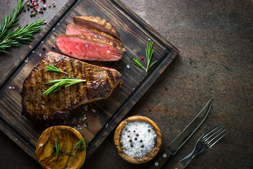 Poster de jardin Steakhouse Grilled beef steak on wooden board. Top view copy space.