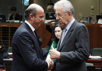 Spain's Economy Minister de Guindos listens to Italy's PM Monti during an EU finance ministers meeting in Brussels