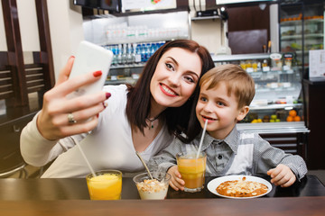 A young mother makes selfie with her little son at a table in a cafe