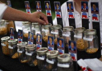 A man places a corn kernel in a jar as he places a vote for U.S. Republican presidential candidate and former Minnesota Governor Tim Pawlenty at the Iowa State Fair in Des Moines, Iowa