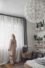 Rear view of woman standing by window in bedroom