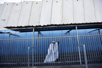 Palestinians walk near the controversial Israeli barrier as they cross into Jerusalem at checkpoint in Bethlehem