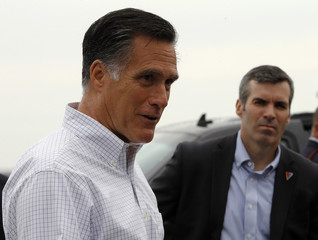 Republican presidential candidate and former Massachusetts Governor Mitt Romney answers questions from reporters as senior advisor Kevin Madden (R) listens at the airport in Sergeant Bluff, Iowa