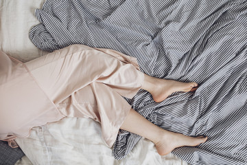 From above photo of legs of woman lying on bed in pyjama.