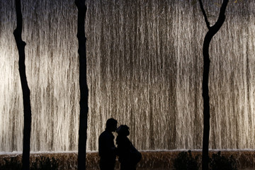 A couple is silhouetted as they kiss in front of a wall waterfall in a small park in New York City
