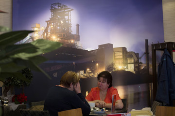 Woman sit in a cafe in front of a picture of the town's steel furnace in the town of Eisenhuettenstadt