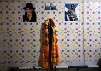 Pictures of Michael Jackson are hung on a wall in a small one-room house Zhang Guanhui, a Michael Jackson impersonator, in Beijing