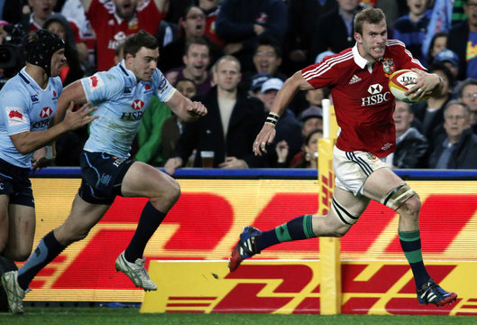 British and Irish Lions player Tom Croft runs to score a try as he is chased by New South Wales Waratahs players Rob Horne and Brendan McKibbin during their rugby union game at the Sydney Football Stadium