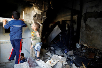 Children play inside a devastated house struck by rocket fire from Syria in Turkey's southeastern border town of Kilis