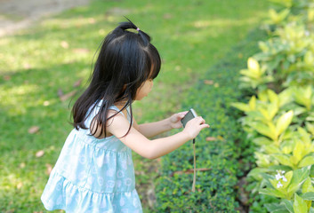 Child girl taking pictures on camera in the garden, Focus at child