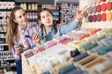 portrait of  mother and daughter  choosing paint color in jar in art shop