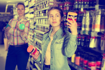 Mother and daughter holding jar with color paint