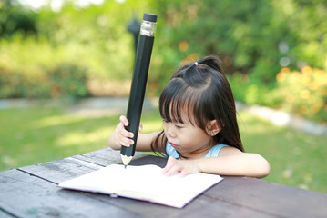 Little child girl writing on table in the garden, Education concept.