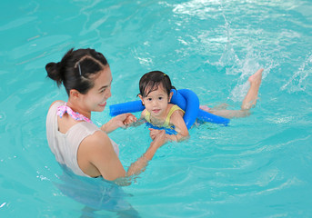 family of mother teaching kid in swimming pool.