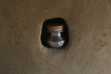 A pot of milk is covered with a bowl and placed in a hole in wall, at a home belonging to a cotton picker's family in Meeran Pur village, north of Karachi
