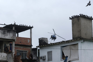 Residents look on as a police helicopter patrols the Manguinhos slum during a peacekeeping operation in Rio de Janeiro
