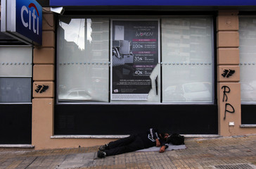 A man sleeps outside a Citibank branch where two stencils with the shapes of the Falkland Islands were painted on near the British embassy in Buenos Aires