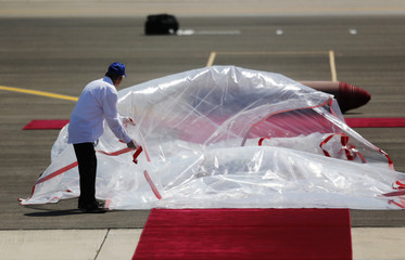 A worker removes plastic sheeting as the red carpet is prepared for U.S. President Obama's arrival at Ben Gurion International Airport