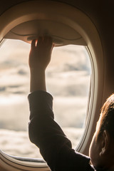 Child looking through the window in an airplane.