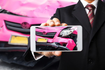 Hand of sale man holding mobile phone with car accident picture for insurance