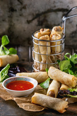 Fried spring rolls with red pepper sauce, served on paper and in fry basket with fresh green salad over old metal texture background. Top view. Asian food