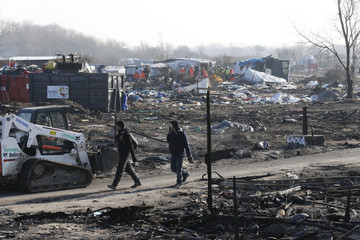 """Migrants walk in the dismantled area of the camp for migrants called the """"Jungle"""", in Calais"""