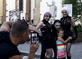 A man takes picture of young girl posing with participants of the Castle Party in front of the church in Bolkow