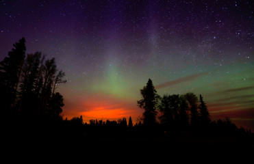 The wildfires glow underneath The Northern Lights, also known as the Aurora Borealis, near Fort McMurray