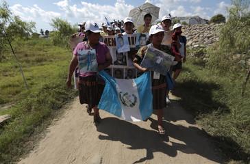 "Women from ""Caravana de Madres Centroamericanas"" display photos of missing migrants and a Guatemalan flag in Ciudad Hidalgo"