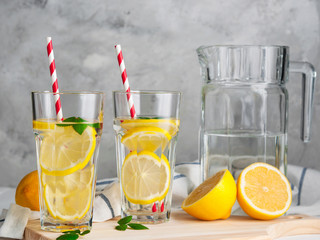 Fresh citrus lemonade in the glasses,concrete grey background, place for text.