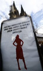 "A placard with a red silhouette of a woman is pictured during the ""Rosenmontag"" (Rose Monday) parade, the highlight of the annual carnival season in Cologne"