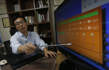 Fortune teller Song Byung-chang looks at a child's fate, or Saju in Korean, at his office in Seoul