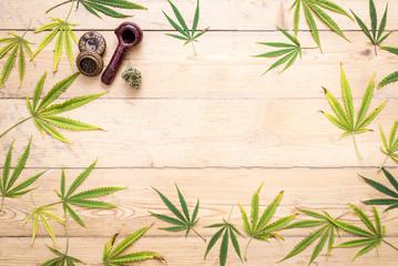 Tobacco pipe, marijuana leaves (cannabis), hemp for smoking on wooden background