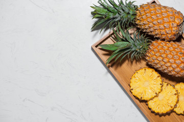 Top view of fresh sliced pineapple on a marble background.