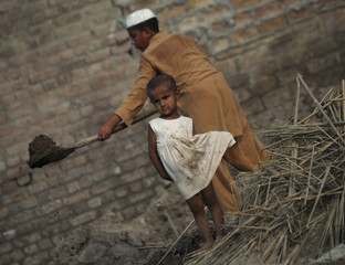 A flood victim stands near her older brother as he removes the rubble from his family's house after it was destroyed by floods in Mohib Banda