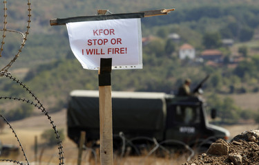 KFOR soldiers sit in their vehicle near the closed Serbia-Kosovo border crossing of Jarinje
