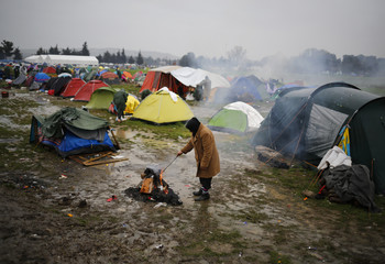 A migrant stands by a fire at a makeshift camp on the Greek-Macedonian border, near the village of Idomeni