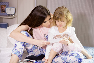 Young mother playing with blond little daughter on bed showing picture