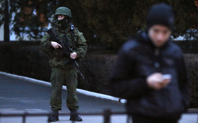 An armed man stands guard at the airport in Simferopol