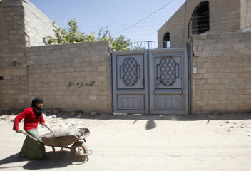 A girl pushes a trolley past the house of a woman believed to be involved in sending explosive packages bound for the United States, in Sanaa