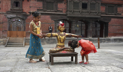 """Young girl taking part in """"Kumari Puja festival"""" bows her head at a statue of God Indra in Kathmandu"""